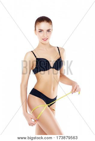 Fit, healthy and sporty woman in black swimsuit isolated on white. Beautiful girl measuring her body. Sport, fitness, diet, weight loss and healthcare concept.
