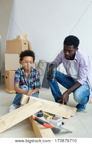 Young man working with power-tool with son near by