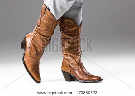 The female legs in jeans and cowboys boots on gray studio background close up