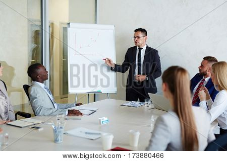 Experienced businessman explaining graph of financial increase to young managers