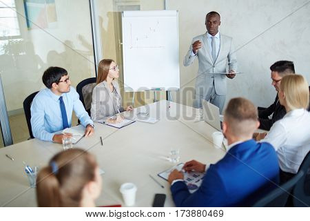 Serious managers listening to confident businessman explanations