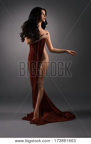 Gorgeous longhaired brunette with perfect body posing wrapped in vinous cloth demonstrating her slim heap studio shot