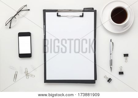 Top view accessories office desk concept.mobile phone coffee notepaper pencil clipboard on white office desk.