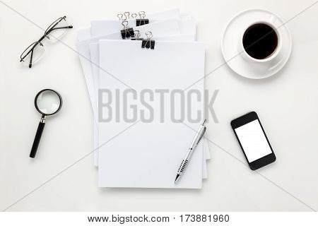 Top view accessories office desk concept.mobile phone coffee note paper pen on white office desk.
