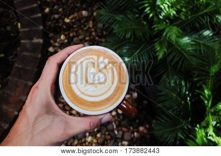 Barista Hand Holding Cup Of Coffee With His Latte Art