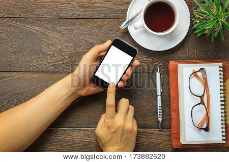 Top view business man using mobile phone and pen notebook eyeglasses cactus on wooden office desk background.