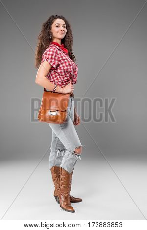 The cowgirl fashion woman over a gray studio background