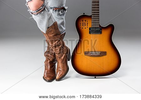 The female legs in ripped jeans and cowboys boots on gray studio background close up