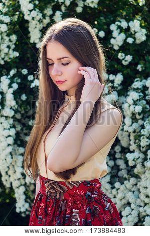 Sensuallity Brunette Girl Posing Against Blooming Tree.