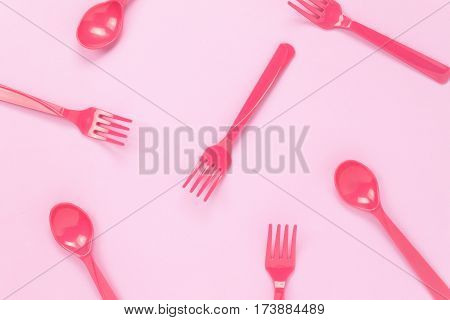 Top view colorful plastic spoon on pink table background with copy space.