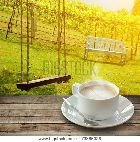 Hot coffee and smoke in white cup over wood with spoon on nature background.