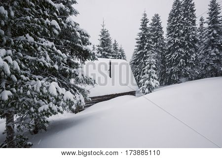 Log Cabin In The Winter Mountains Is Covered With Snow
