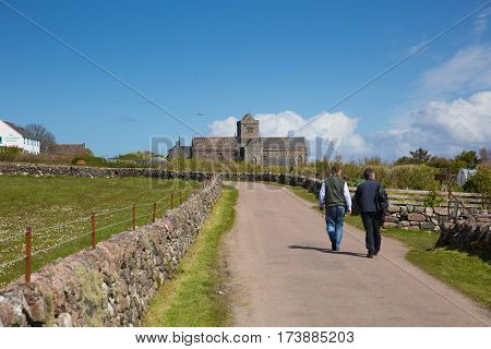 People walking towards Iona Abbey Scotland uk on the Scottish island off the Isle of Mull west coast of Scotland