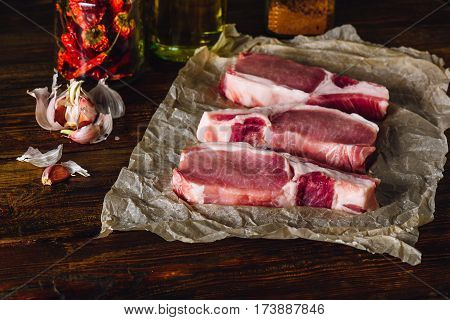 Three Raw Pork Loin Steaks with Garlic Dry Chili Pepper and Olive Oil.