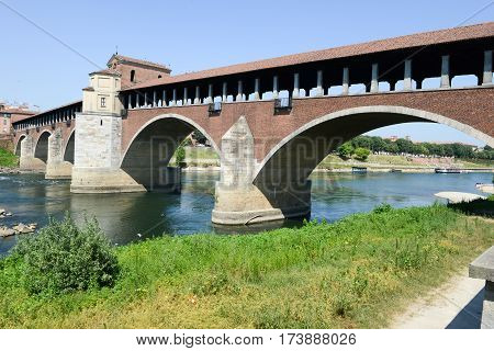 Pavia, Italy - 14 June 2015: Covered bridge over the river Ticino. Very quaint has five arches and is completely covered with two portals at the ends and a small chapel religious center
