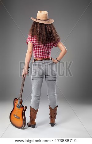 The back view of cowgirl fashion woman with acoustic guitar over a gray studio background