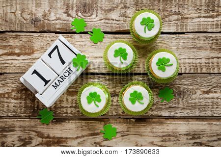 Green paper clover leafs and tasty cupcakes on a grey wooden table