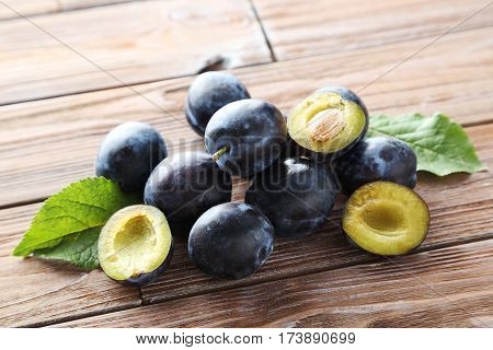 Tasty And Ripe Plums On Brown Wooden Table