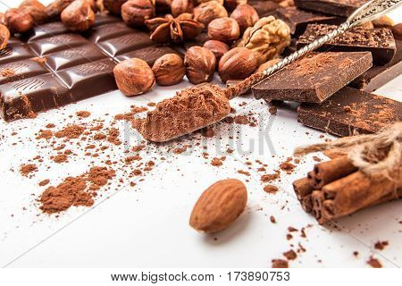 Chocolate Pieces, Cocoa Powder, Chocolate Shavings, Filbert, Cinnamon On White Background.