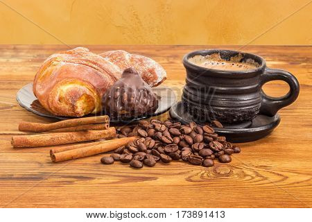 Freshly brewed coffee with milk in the black ceramic cup scattered beside roasted coffee beans and cinnamon sticks chocolate truffle and croissant on the glass saucer on the old wooden surface