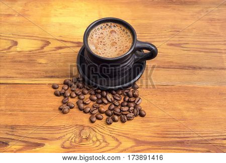 Freshly brewed coffee with milk in the black ceramic cup with saucer and scattered near coffee beans on a surface of an old wooden planks