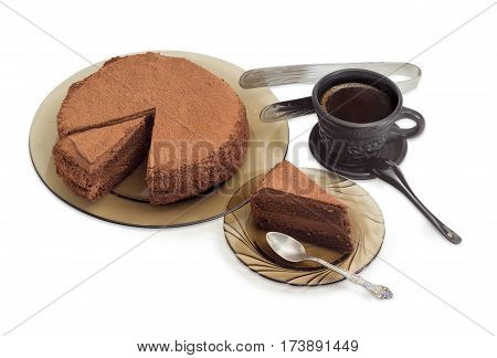 Partly sliced round chocolate cake sprinkled with cocoa powder on a glass dish piece of the cake with spoon on the glass saucer and black coffee in black ceramic cup on a light background