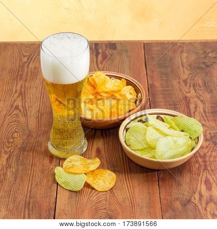 Beer glassware with lager beer potato chip flavored paprika and wasabi in two different ceramic bowls and several potato chips separately beside on an old wooden surface