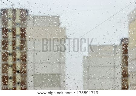 Background of the window pane with the streams and drops of water and blurred apartment buildings through the glass during a rain