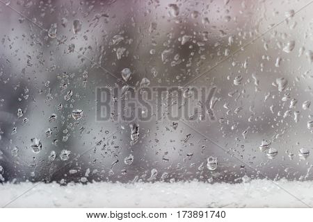 Background from a streams and drops of water on the window pane and strip of the wet snow at the bottom during a rain with sleet