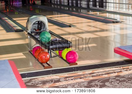 Playing area with several lanes with bowling pins and ball return device with colored bowling balls on the foreground in the modern pin bowling alley