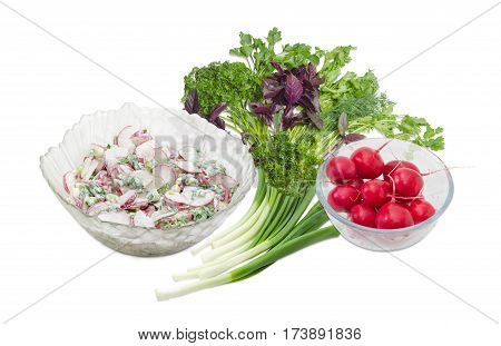 Salad of the sliced red radish green onion with sour cream in the glass salad bowl and separately whole red radish in glass bowl bundle of the green onion and greens on a light background
