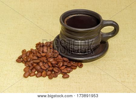 Freshly brewed black coffee in the black ceramic cup with saucer and a pile of the roasted coffee beans beside on the surface covered with hessian