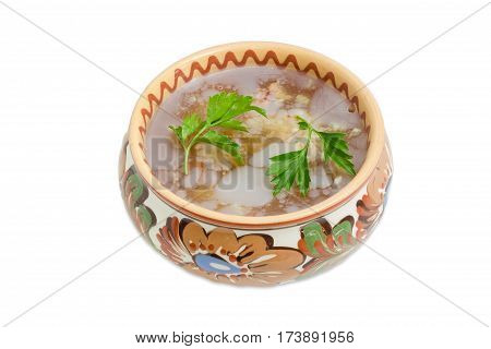 Pork aspic decorated with twigs of parsley in the ceramic bowl with a floral ornament on a light background