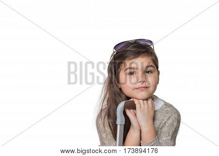Studio shot of cool little girl tourist with glasses on her head leaning on the handle of a suitcase and looking at the camera. All is on the white background.
