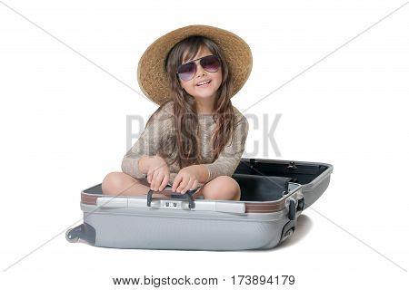 Studio shot of smiling little girl tourist with straw hat and glasses sitting in the suitcase. All is on the white background.