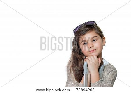 Studio shot of cool little girl tourist with tilted head leaning on the handle of a suitcase and looking at the camera. All is on the white background.