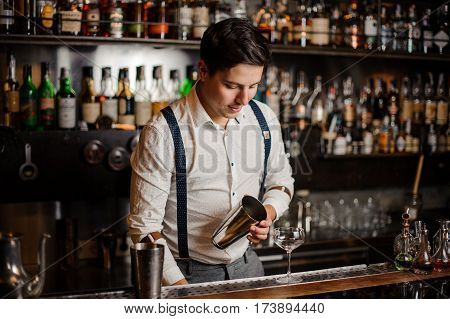 Bartender in white shirt is making a coctail at the bar counter