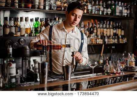 Bartender in white shirt is making an alcohol coctail