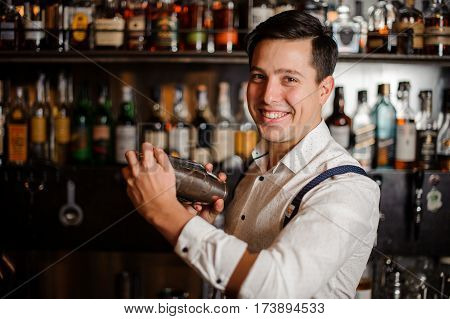 smiling bartender is shaking a fancy coctail