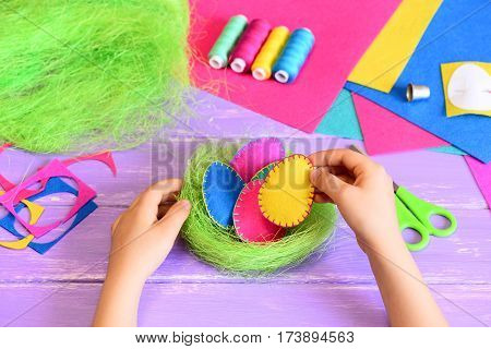 Small child makes a simple Easter decoration. Child puts a yellow felt egg in a sisal nest with eggs. Crafts supplies on a table. Bright Easter DIY idea for children