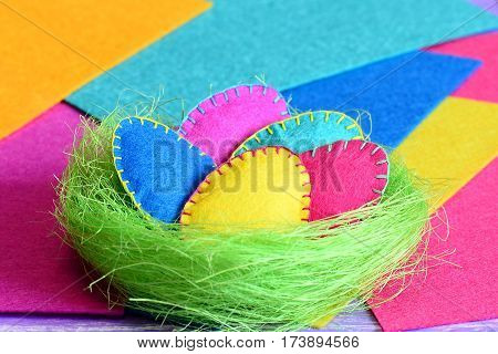 Easter eggs in a nest crafts. Homemade felt Easter eggs in a green sisal nest isolated on colorful felt background. Crafts for decorating a room for Easter. Closeup