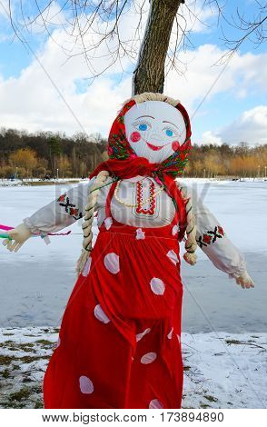 Shrovetide doll in colorful headscarf and sarafan on background of spring landscape