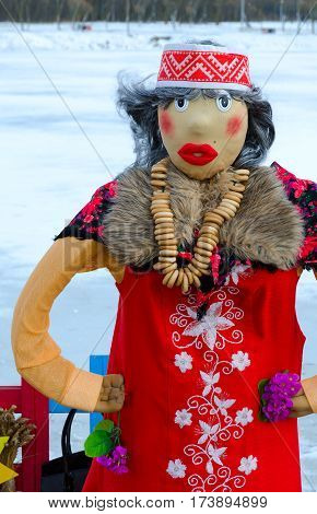 Shrovetide doll in red sundress with embroidery and colorful shawl with bunch of bagels on neck