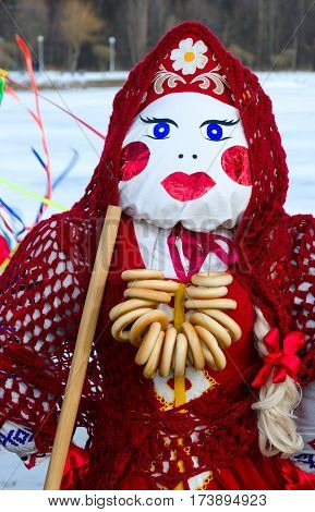Shrovetide doll in red costume and knitted shawl with bunch of bagels on neck