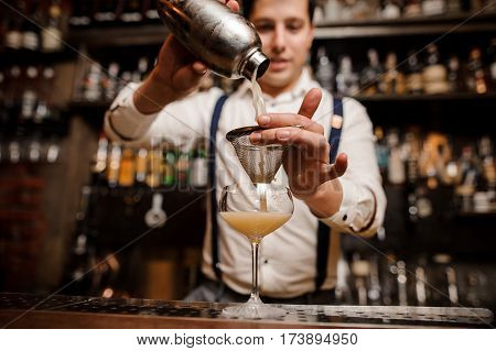 bartender is pouring coctail into the glass
