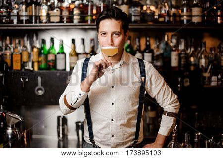 bartender in white shirt with coctail at the bar stand