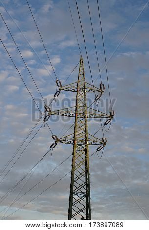 Tall electric pylon leading high current and voltage as a symbol of electricity and technological progress with positive background made of bright clouds before sunset