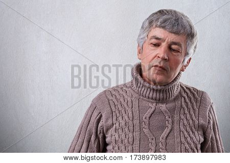 A sad senior man looking thoughtful down dressed in sweater. A wrinlked elderly man with gray hair thinking about his life having thoughtful and sad expression isolated over white background