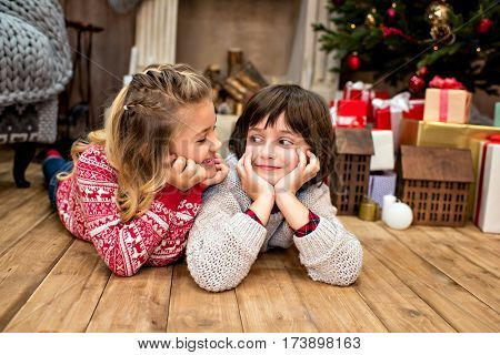 Happy kids lying on floor near a pile of gifts and looking at each other