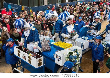 carnevalists on a parade vehicle giving awy flowers - carnival in cologne - Participants of the rose monday parade in cologne on February 27, 2017